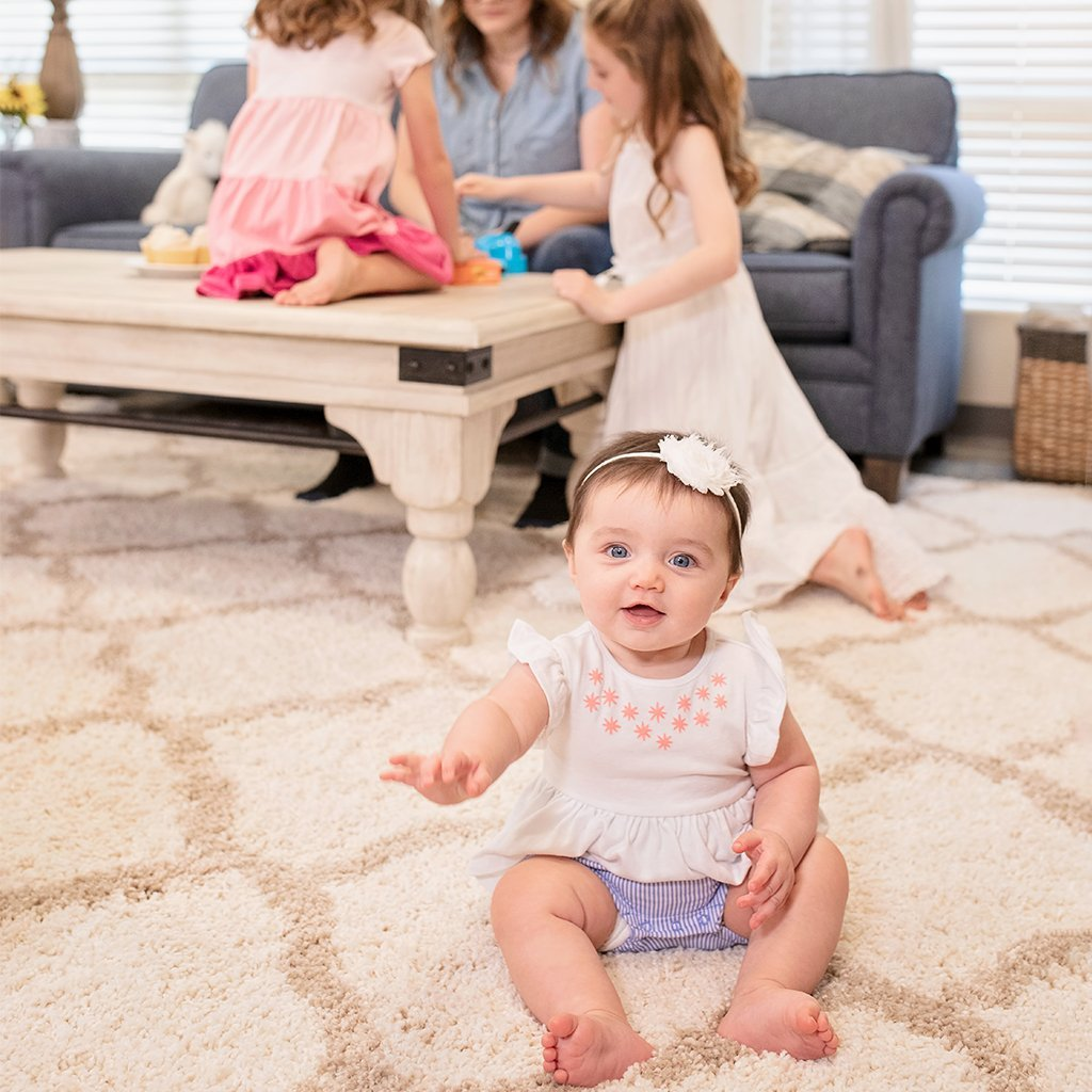 About us baby looking at camera on living room floor